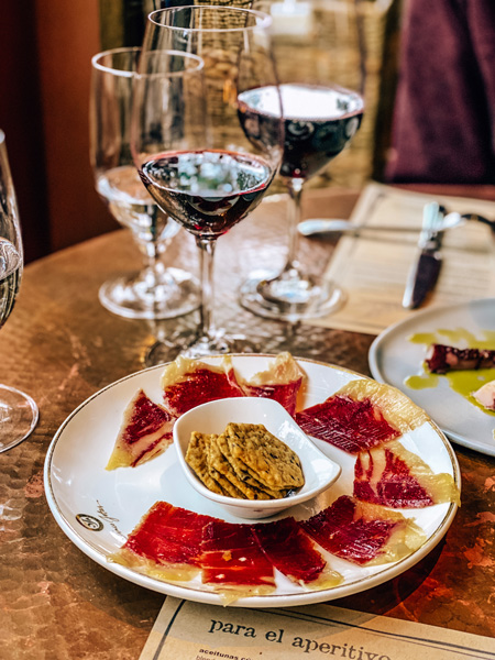 Jamon Charcuterie at Curate Asheville with two red wine glasses
