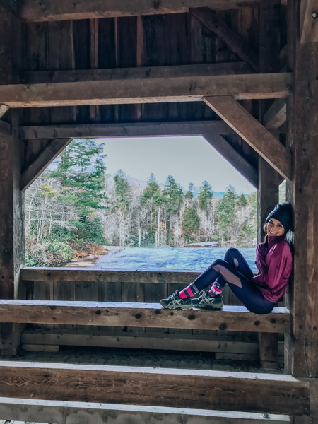 High falls covered bridge DuPont State forest with brunette white woman dressed for winter with a hat sitting on bridge