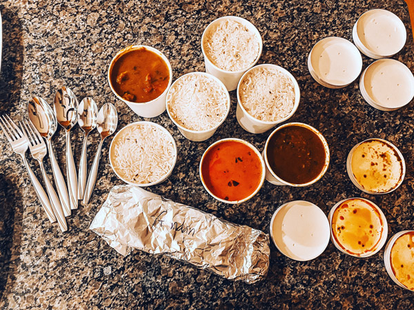 Mela Asheville Indian food takeout containers with white rice, silverware, daal, tandoori chicken, and chicken tikka masala