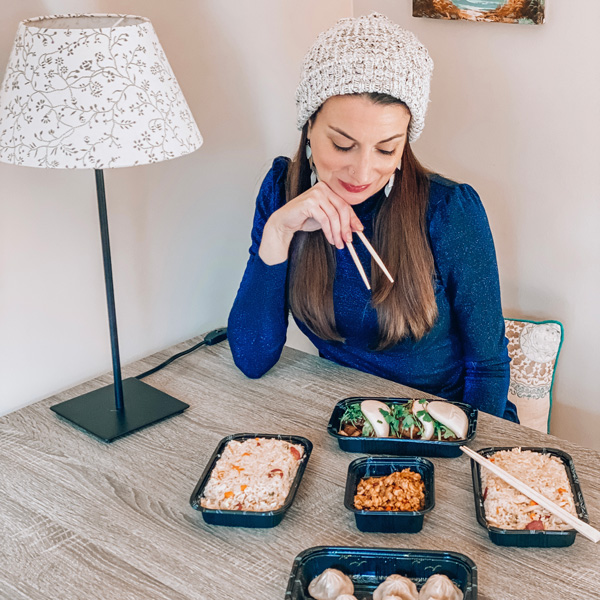 Red Ginger Dimsum and Tapas Asheville takeout with white brunette woman wearing a white hat and holding chopsticks with rice, dumplings and takeout containers