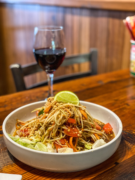 Thai Pearl Thai Papaya Salad with salad in white bowl garnished with lime and glass of wine in the background on a brown table