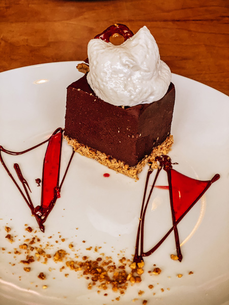 Vegan Dessert Plant Asheville chocolate cake on crust with whipped cream, red sauce, and nuts