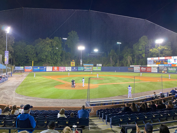 Asheville Tourists Baseball Game with baseball McCormick Field at night with players around the bases
