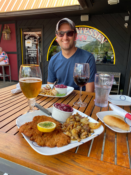 Haus Heidelberg German Restaurant Hendersonville NC white brunette male with two plates of potatoes, meat, beer, and white