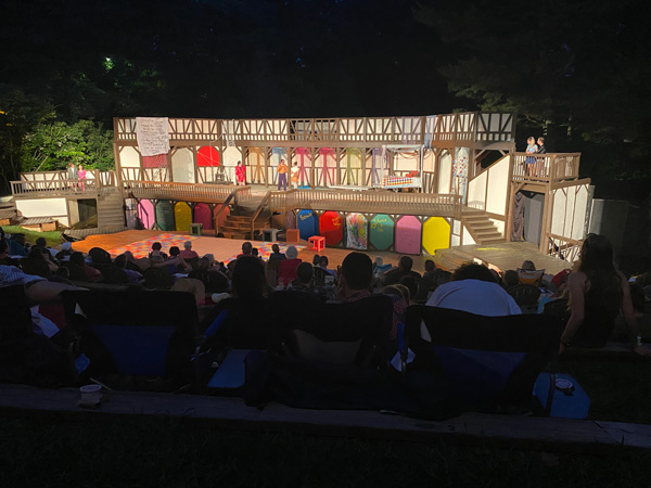 Montford Park Players Shakespeare in the Park with old fashioned stage lit up at night with people sitting in front