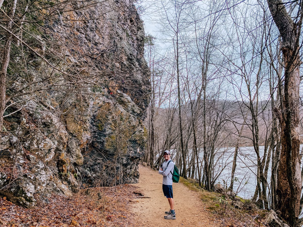 Appalachian Trail Lover's Leap Loop Hot Springs NC with white white brunette male with green backpack and hat standing in front of a rock and French Broad River
