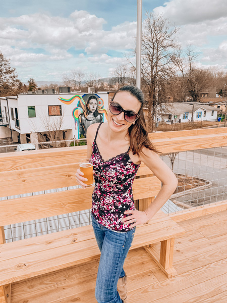 Archetype Brewing West Asheville with white brunette female wearing flowered shirt, jeans, and sunglasses holding a white ale in front of street art on a rooftop seating area