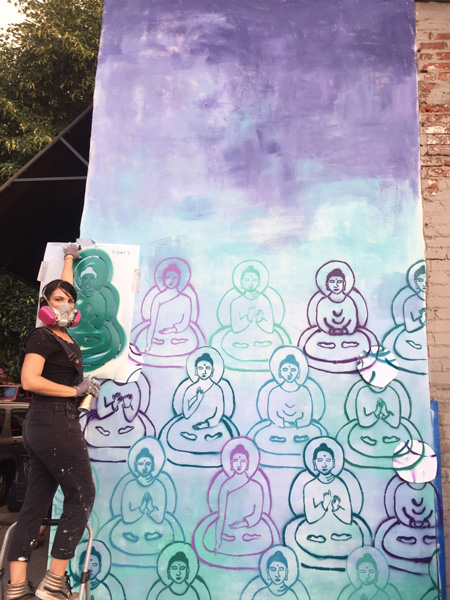 Asheville Murals Buddhas Downtown with artist Amanda Giacomini in front of purple, green and blue Buddhas