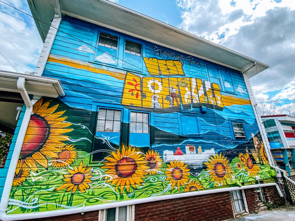 Best Neighborhoods In Asheville West Asheville Mural with house with greetings from West Asheville mural with blue sky and sunflowers