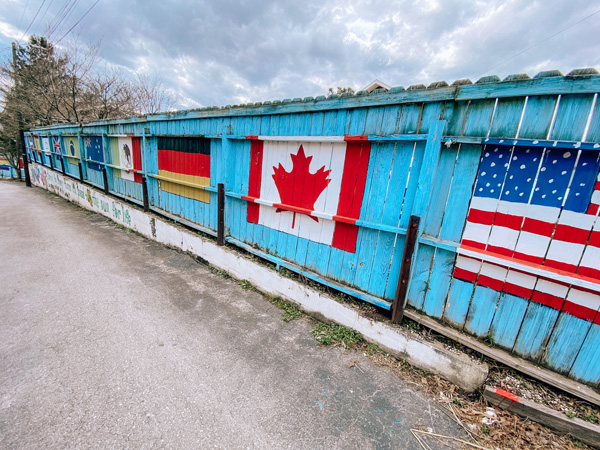 Bon Paul & Sharky's Hostel Country Flags mural with the United States and Canadian flags on a blue fence in West Asheville NC