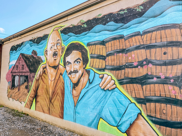 Burial Beer Co Tom Selleck Sloth Mural Asheville with Sloth's arm around Selleck next to barrels and a barn