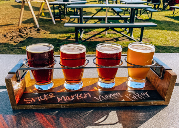 Burning Blush Brewery Near Brevard with flight of four amber to golden ales and picnic tables