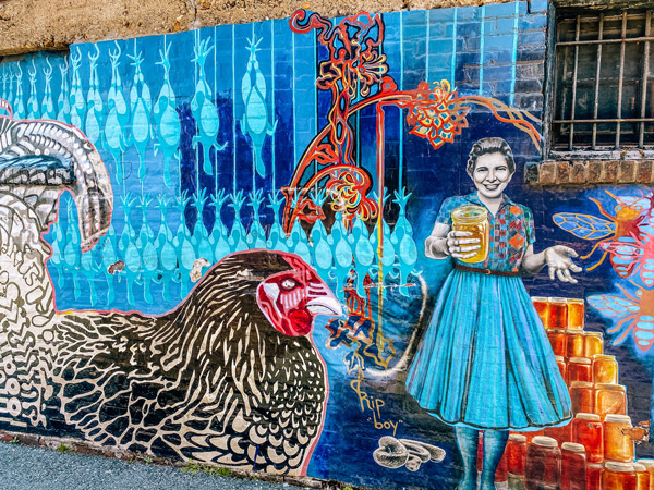 Chicken Alley Asheville mural with Sandra Gudger holding and selling honey next to chicken and rooster