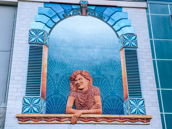 Daydreamer Aloft Mural Asheville Alex Irvine and Ian Wilkinson  woman leaning out of a window and daydreaming made from tiles and ceramics