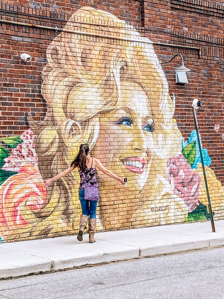 Dolly Parton Mural West Asheville Neighborhood with white  brunette woman running up to Dolly Parton face on a street mural