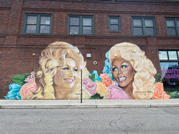 Dolly Parton and RuPaul Mural West Asheville NC with portrait of her head and blue and pink flowers