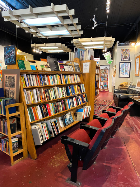 Downtown Books & News Used Bookstore Asheville with old red movie theater chairs in front of bookshelf filled with books