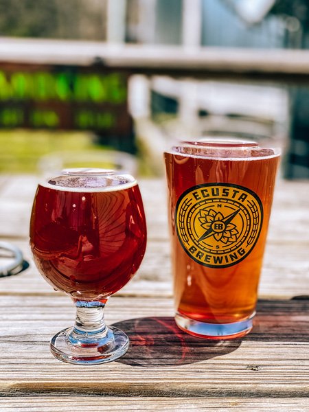 Ecusta Brewing Company Brevard NC with amber colored beer and mixed berry cider in Ecusta beer glass