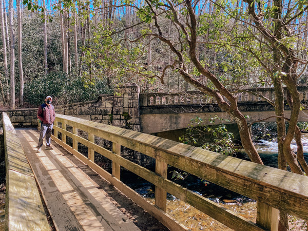 Entrance Moore Cove Falls Trail NC with white male in garnet colored coat standing on a wooden bridge