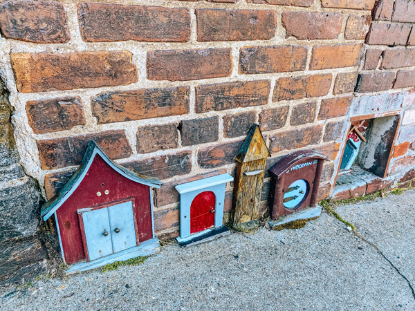 fairy houses Woodfin Street Asheville NC with small houses attached to brick wall