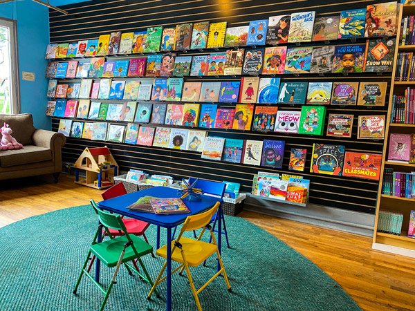 Firestorm Books & Coffee with children's section with colorful table and chairs and full book display along the wall