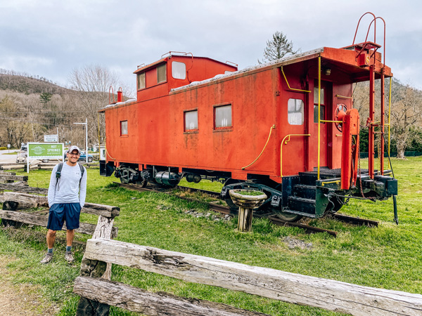 Lover's Leap Hike Loop Hot Springs NC with white brunette male with green backpack and hat standing in front of red caboose