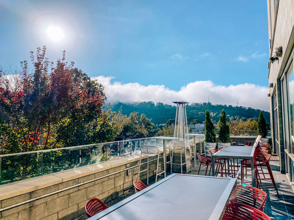 Ledge at Aloft Downtown Asheville NC Hotel with blue sky, fall foliage red trees, and outdoor patio with tables and chairs