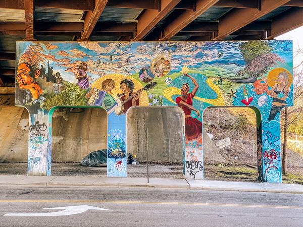 Lexington Gateway Mural Asheville NC with colorful portraits under a highway bridge on columns