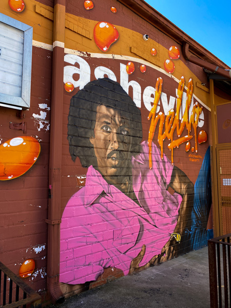 Lionel Richie Mural by Gus Cutty The Orange Peel Asheville with Richie, a Black man, wearing a hot pink shirt and jeans
