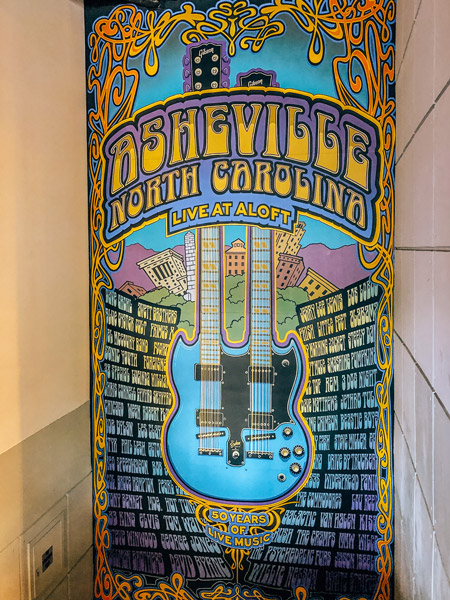 Live At Aloft Downtown Asheville Mural with blue guitar and names of music artists