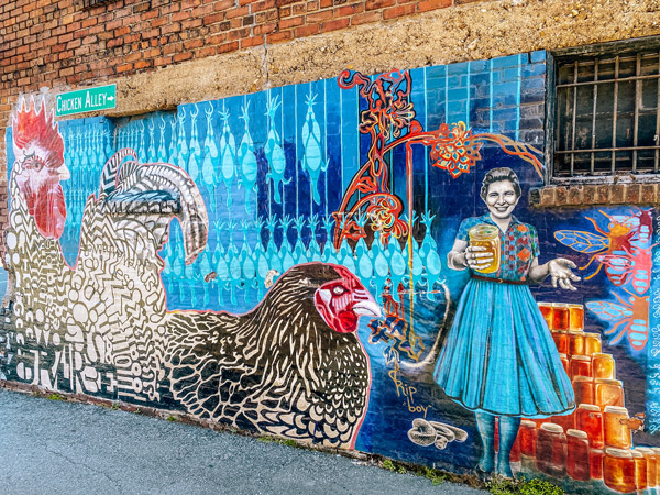 Molly Must Chicken Alley Mural Asheville NC with 10 foot rooster, chicken sitting down, and woman holding and selling jars of honey
