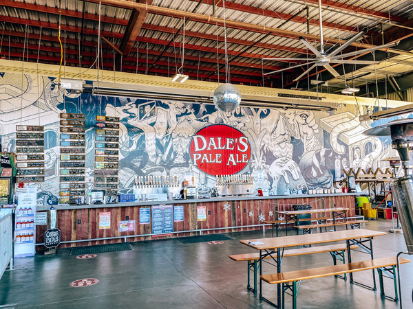 Oskar Blues Brewing Brevard NC with picture of taproom with Dale's Pale Ale on wall, picnic tables, and bar area