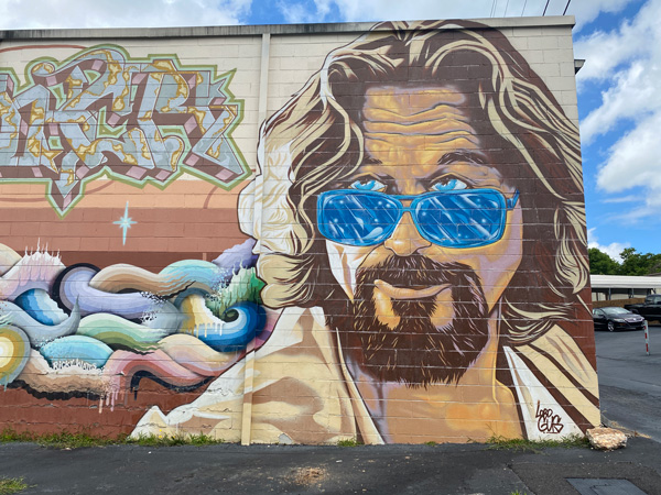 The Big Lebowski Mural Asheville with the character The Dude from the movie as a white male with sandy brown blonde hair, blue sunglasses, and goatee