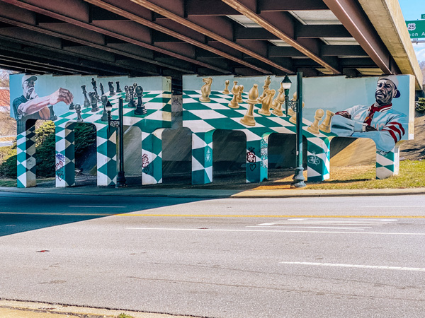 The Chess Players Murals Asheville NC with chess broad painted under highway bridge