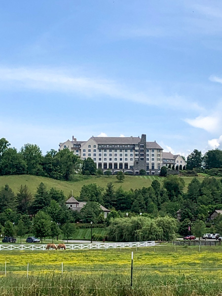 The Inn On Biltmore Estate with hotel on hill, green grass, and two horses
