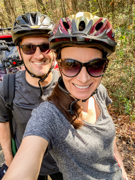 Fun things to do in Asheville mountain biking at Bent Creek Experimental Forest with white brunette male and female wearing bike helmets in gray shirts with sunglasses