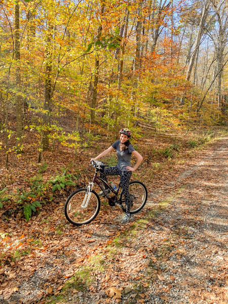 Bent Creek Experimental Forest Mountain Biking Trails Asheville with white brunette woman on purple mountain bike on trail surrounded by fall foliage