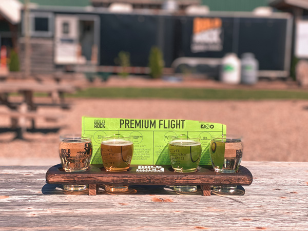 Bold Rock Cidery Mills River Premium Flight with four clear to light brown ciders in a flight with tasters and green paper naming the ciders