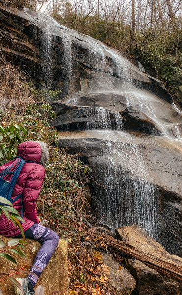 Daniel Ridge Falls Trail with woman in garnet colored winter coat with hood and purple hiking leggings sitting on a rock and looking at waterfall