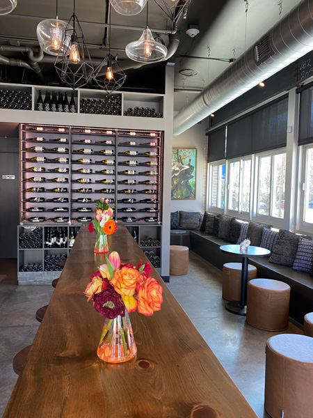 Marked Tree Vineyard Asheville Tasting Room with wine bottles on wall, orange flowers and tables with chairs