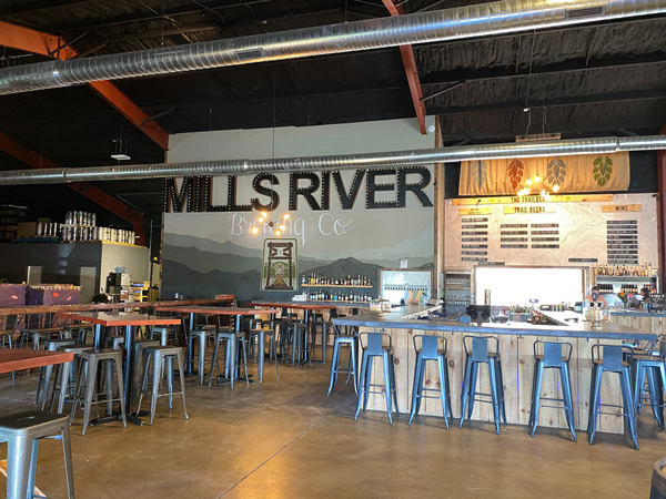Mills River Brewing Co Taproom with bar, bar tables, craft beer taps, and bar seating.
