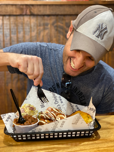 Moe's Original BBQ with white brunette male wearing a NY Yankees hat eating smoked chicken from a basket with sides like baked beans and potato salad