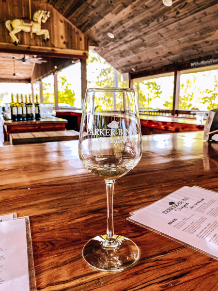 Parker Binns Vineyard Tryon Foothills NC with wine tasting glass under covered outdoor seating and bar with menus and wine bottles
