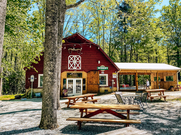 Sawyer Springs Vineyard Hendersonville NC with red barn, picnic tables, and tree