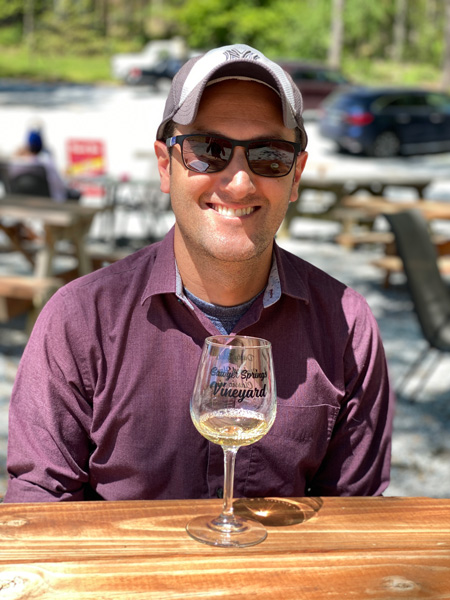 Sawyer Springs Vineyard Near Asheville portrait of white male wearing sunglasses and hat in purple shirt with white wine tasting glass