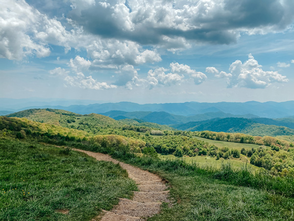 Appalachian Trail Max Patch Hike with dirt path, blue mountains, and green trees