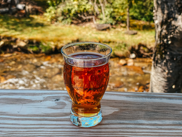 Bearwaters Brewing Company Maggie Valley NC with beer flight glass filled with amber colored ale sitting on a railing with river in the background