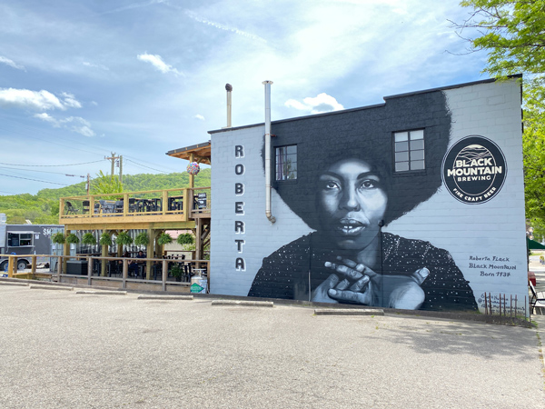 Black Mountain Brewing Roberta Flack Mural with portrait of Flack and upper and lower deck with brewing building