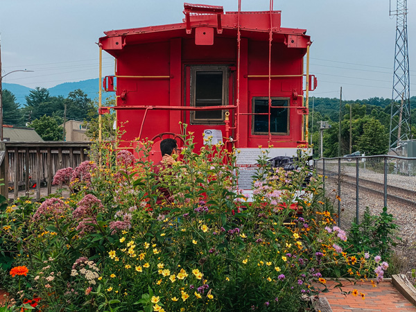 Black Mountain Old Depot with red train caboose, flowers, and mountains and train tracks in the background