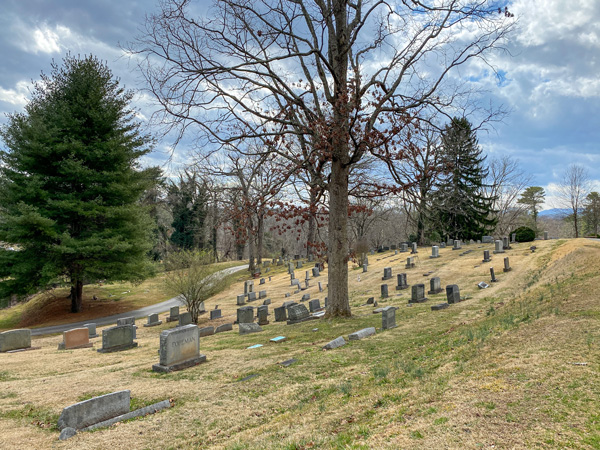 Historic Riverside Cemetery Montford with picture of rolling green hill, blue sky, a bare tree, and gravestones